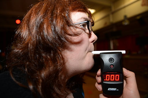 Red head woman blowing into a breathalyzer